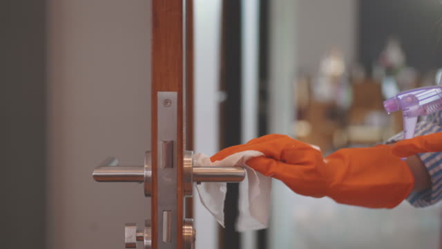woman using alcohol based sanitizer spray on door knob for disinfecting coronavirus or covid-19 - cleaning glove stock videos & royalty-free footage