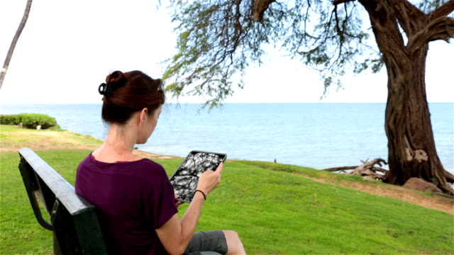 woman using an electronic tablet on a bench - pacific islands stock videos & royalty-free footage