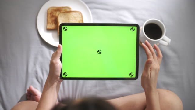 woman using and looking on digital tablet wit green screen on bed in morning, horizontal - holding stock videos & royalty-free footage