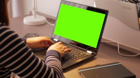 stockvideo's en b-roll-footage met vrouw met behulp van en laptop toetsenbord met een groen scherm - over shoulder