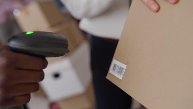 vídeos de stock, filmes e b-roll de mulher usando leitor de código de barras para organizar pedidos de clientes para entrega de envio - pacote arranjo