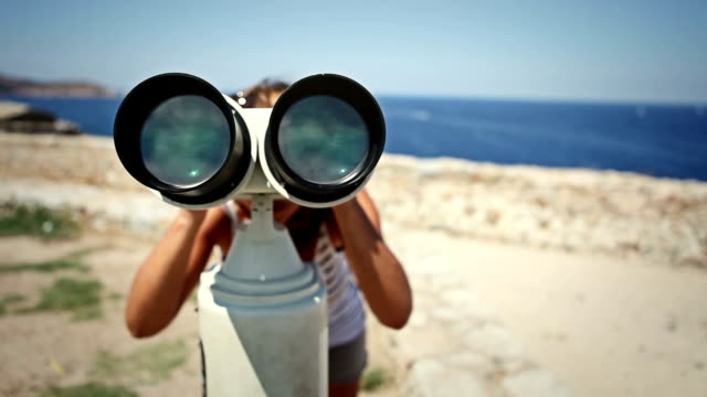 woman using binoculars - looking through an object stock videos and b-roll footage