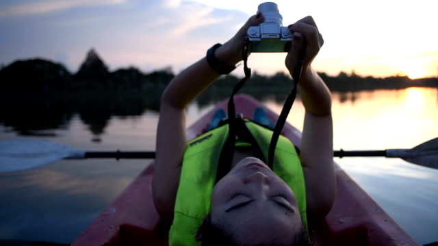 Woman using camera on kayak in twilight evening