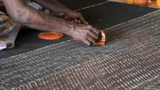 MS Woman using carved wooden comb to create abstract tiwi art / Northern Territory, Australia