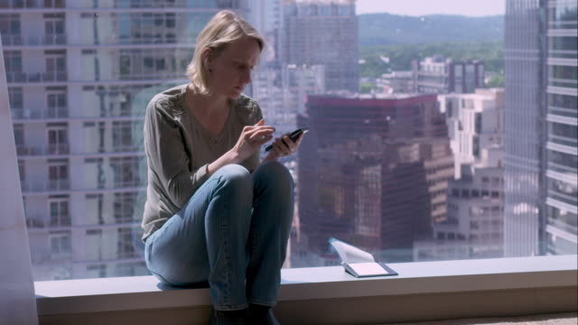 vídeos de stock, filmes e b-roll de woman using cell phone in hotel room overlooking downtown austin - só uma mulher de idade mediana