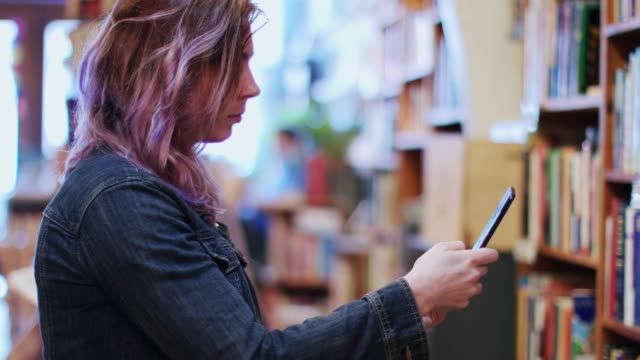 woman using cellphone in bookstore - pink hair stock videos & royalty-free footage