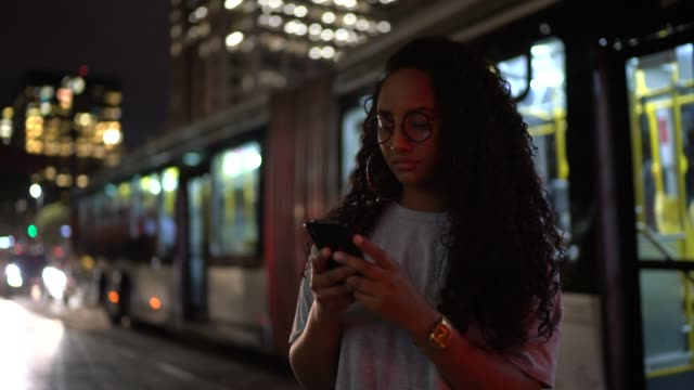 woman using cellphone in the city at night - são paulo stock videos & royalty-free footage