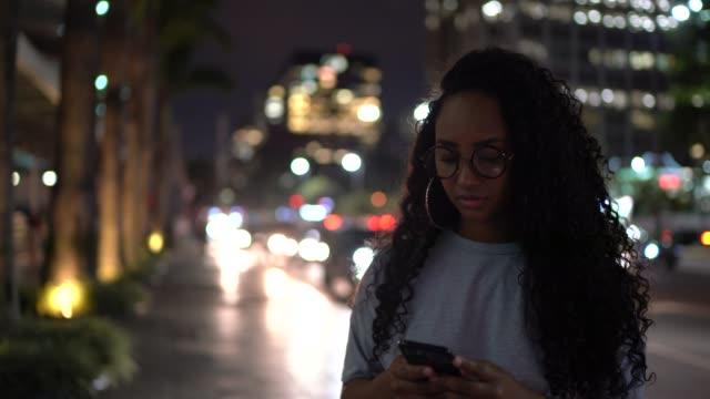 vídeos de stock, filmes e b-roll de mulher que usa o telemóvel na cidade na noite - foco determinação