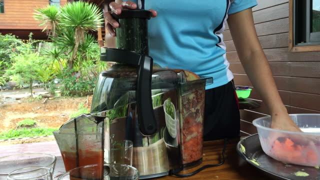 遠心機を使用して果物や野菜のジュースを準備する女性 - 遠心機点の映像素材/bロール