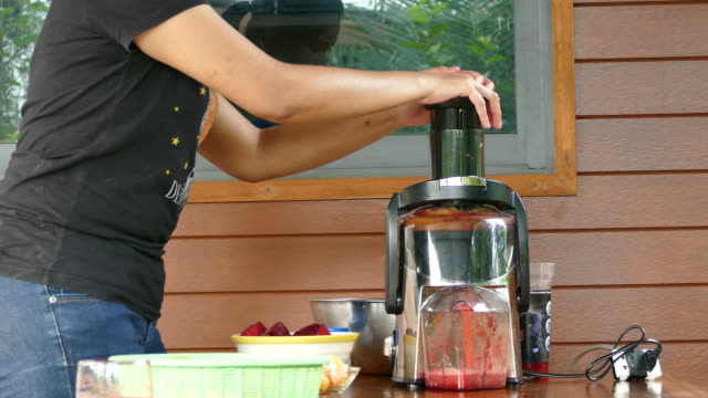 woman using centrifuge machine to prepare fruits and vegetables juice - frutta video stock e b–roll