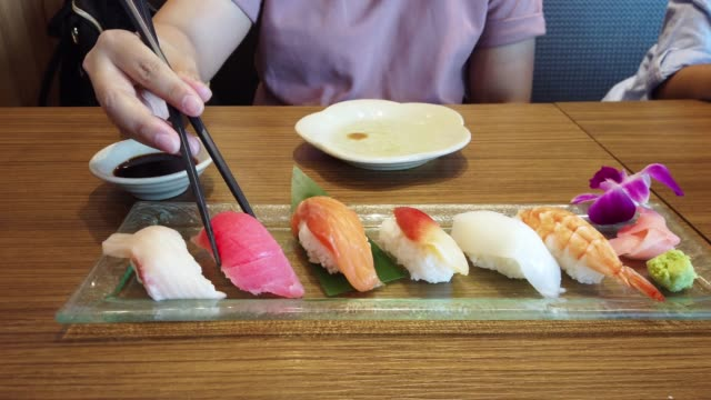 woman using chopsticks pick sushi in japanese cuisine restaurant. - wasabi stock videos and b-roll footage