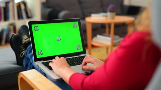 kvinna som använder chroma key screen laptop hemma - över axel perspektiv bildbanksvideor och videomaterial från bakom kulisserna