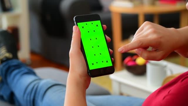 kvinna som använder chroma key screen smart telefon hemma - skrollning bildbanksvideor och videomaterial från bakom kulisserna