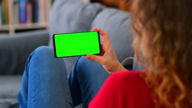 vídeos de stock, filmes e b-roll de mulher usando o smartphone da tela da tecla cromroma em casa - sofá