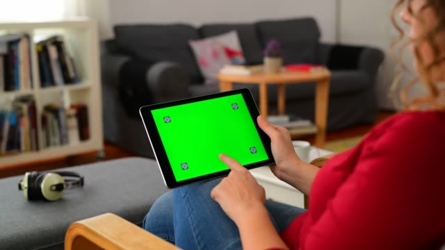 vídeos y material grabado en eventos de stock de mujer usando croma key screen tablet computer en casa - deslizar