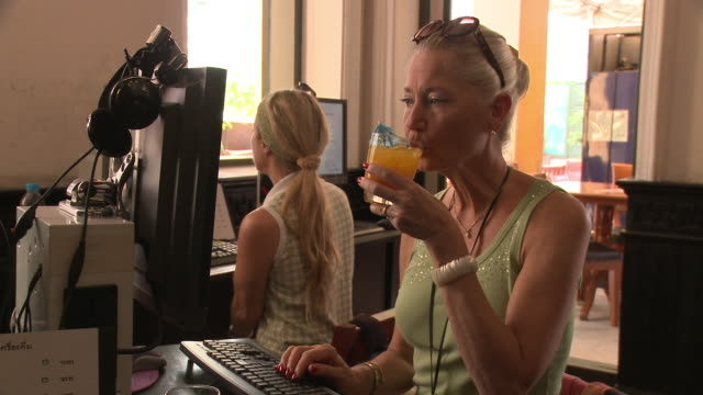 ZI CU Woman using computer and drinking juice in internet cafe, Bangkok, Thailand