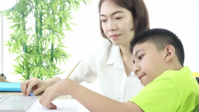 woman using computer for social media knowledge information and teaching drawing to cerebral palsy disabled boy - cerebral palsy stock videos & royalty-free footage
