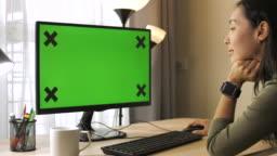Woman using computer green screen at home