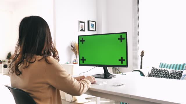 vidéos et rushes de femme utilisant l'écran vert d'ordinateur à la maison - desktop pc
