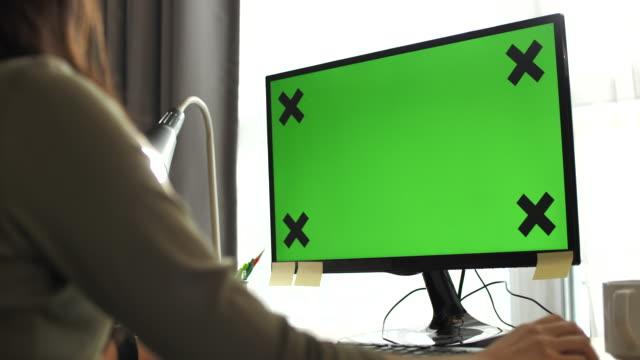 vidéos et rushes de femme utilisant l'écran vert d'ordinateur - utiliser l'ordinateur