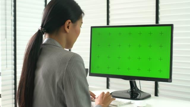 vídeos de stock, filmes e b-roll de mulher usando o computador na tela verde no escritório - modelo web