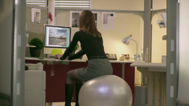 ms zo woman using computer sitting on fitness ball in office, appleton, wisconsin, usa - pallone per fitness video stock e b–roll