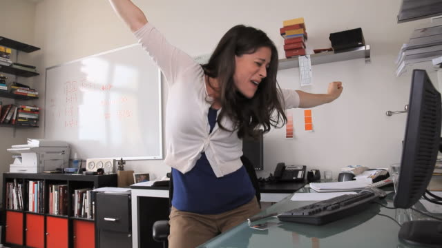 MS Woman using computer then cheering and dancing in office, Jersey City, New Jersey, USA