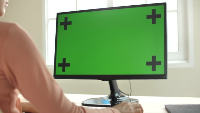 woman using computer with green screen at home - desktop pc stock videos & royalty-free footage