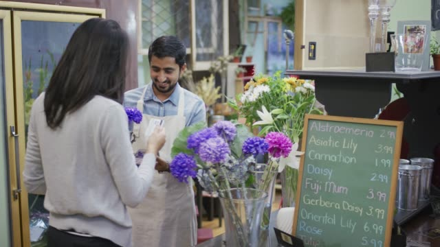 woman using contactless payment with ethnic flower store owner - flower shop stock videos and b-roll footage