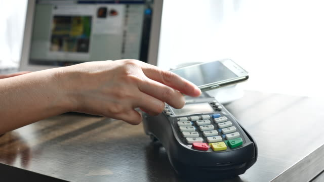 Woman using contactless payment with phone, NFC Payment