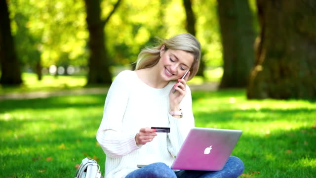 a woman using credit card shopping online with a laptop in the park - ordering stock videos and b-roll footage