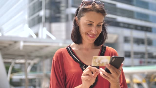 vídeos de stock, filmes e b-roll de mulher usando cartão de crédito com o telefone móvel - mãos cobrindo olhos