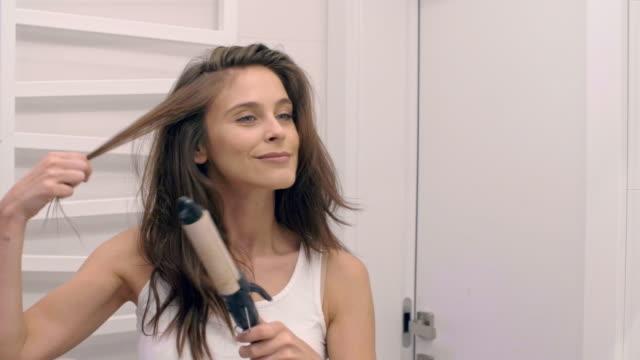 woman using curling iron/ chorzow/ poland - spole bildbanksvideor och videomaterial från bakom kulisserna