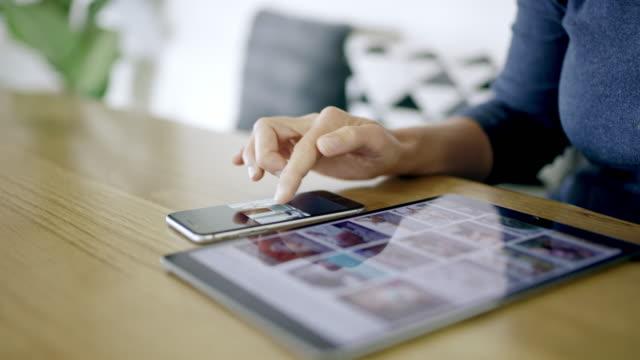 vídeos de stock e filmes b-roll de cu woman using digital tablet and smart phone at table - fotografia imagem