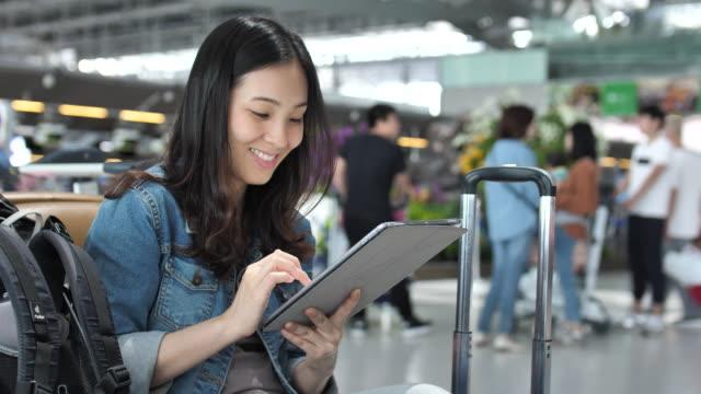 vídeos de stock, filmes e b-roll de mulher usando tablet digital no aeroporto - foco difuso