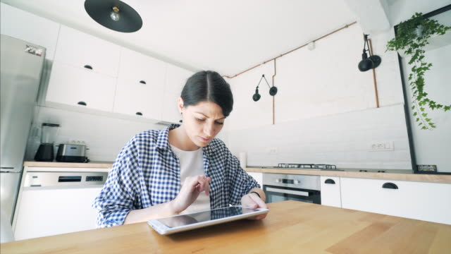 Woman using digital tablet at home.