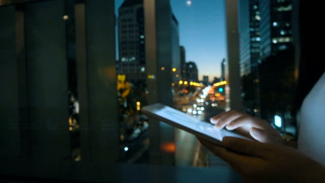 woman using digital tablet at night - business video stock e b–roll