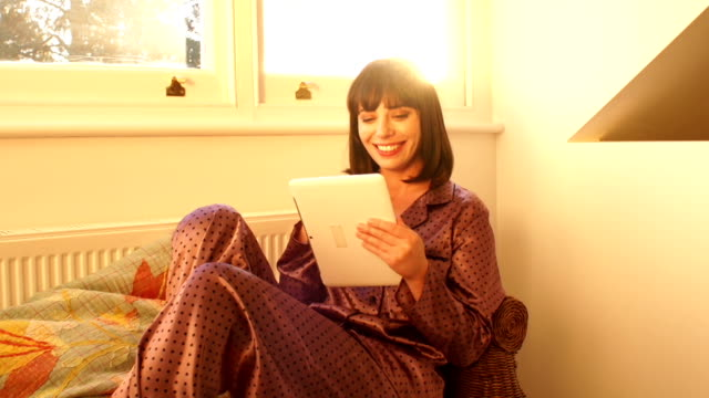 woman using digital tablet by the window - pyjamas stock videos and b-roll footage