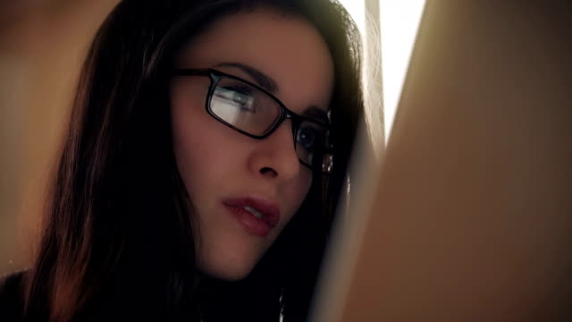 Woman using digital tablet, glasses reflections.