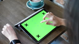 Woman Using Digital tablet green screen in cafe