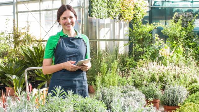 Woman using digital tablet in garden center
