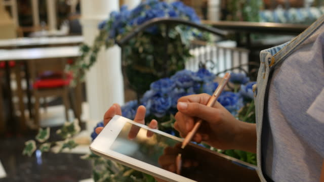 woman using digital tablet in shop - florist stock videos & royalty-free footage