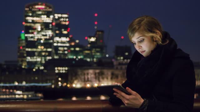 DS vrouw met behulp van digitale tablet in de stad bij nacht
