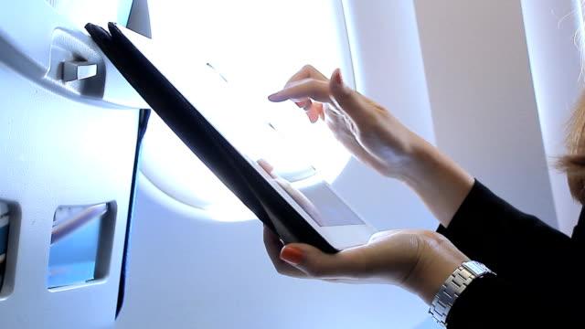 Woman using digital tablet on airplane