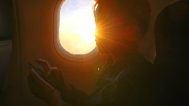 vídeos de stock, filmes e b-roll de mulher usando um tablet digital no avião - correspondência