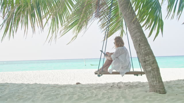 ms woman using digital tablet on palm tree swing on idyllic,tropical ocean beach,maldives - swing stock videos & royalty-free footage