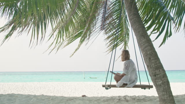 ms woman using digital tablet on palm tree swing on idyllic,tropical ocean beach,maldives - turquoise coloured stock videos & royalty-free footage
