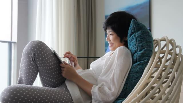 vídeos de stock, filmes e b-roll de hd: mulher usando um tablet digital no sofá - reclinando