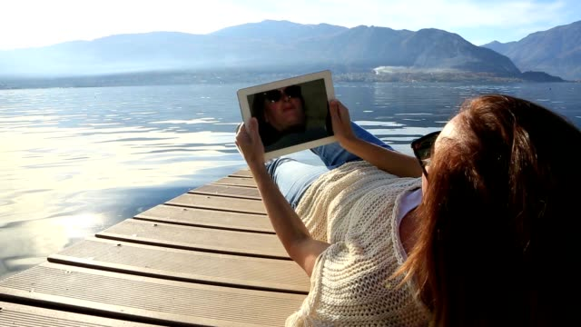 woman using digital tablet on wooden dock - lying on back stock videos & royalty-free footage