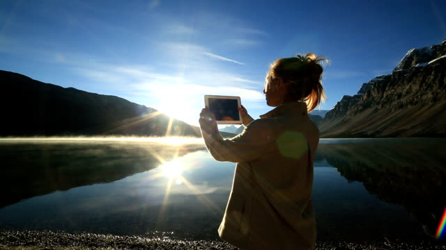 Woman using digital tablet to photograph lake